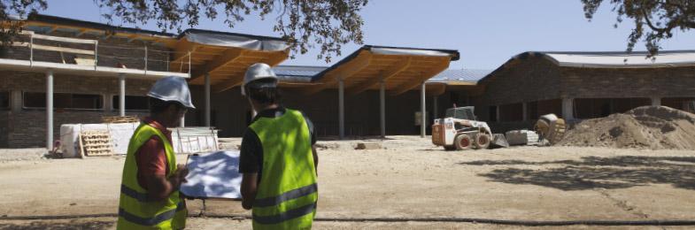 Arquitectos revisando planos delante de edificio en construcción